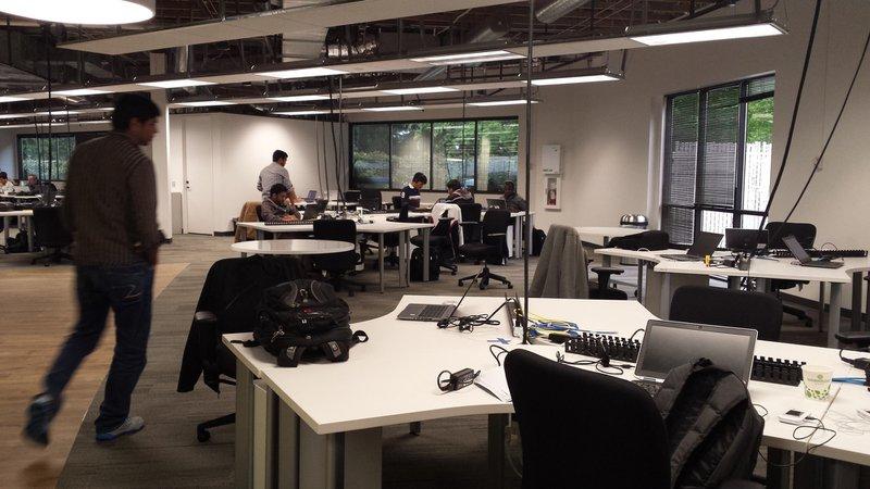 Developer walking through a contemporary open office, open, agile, development space, desks, developers, backpack, laptop computers, Redmond, Washington, USA